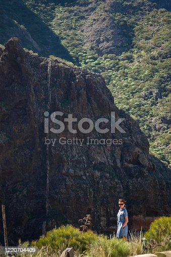 A happy and good looking female wearing a denim skirt standing in the wild, in front of a mountain.