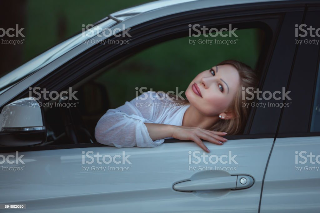 Woman in the window of the car. stock photo