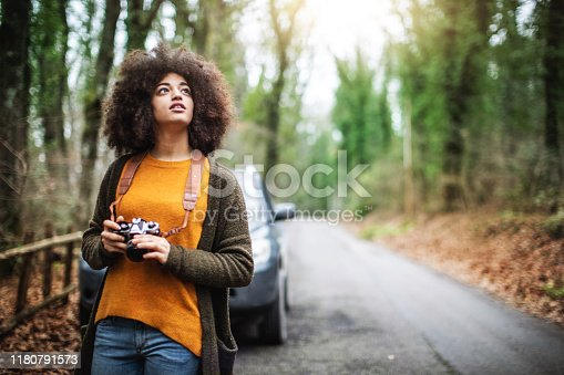 Young woman with afro hairstyle exploring the woods