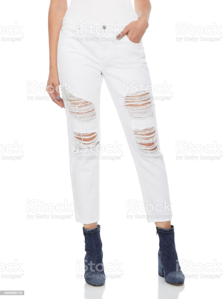 Woman in tight white jeans with black shoes, white background stock photo
