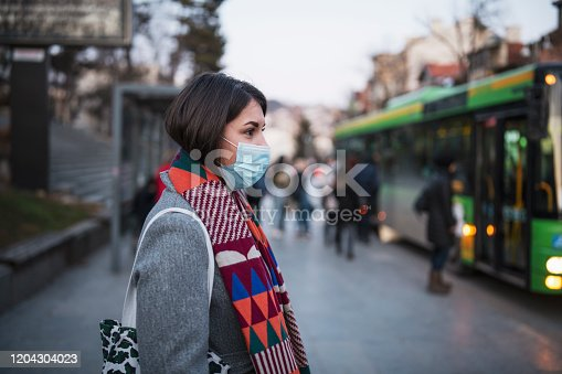 Side view of young woman with protective face mask in town, she standing in front at the bus stop and waiting for her transport after work.