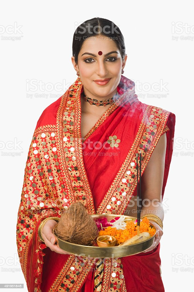 Woman in traditional Assamese mekhla holding religious offering stock photo