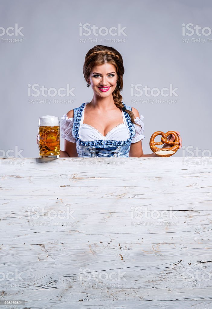 Woman in traditional bavarian dress holding beer and pretzel photo libre de droits