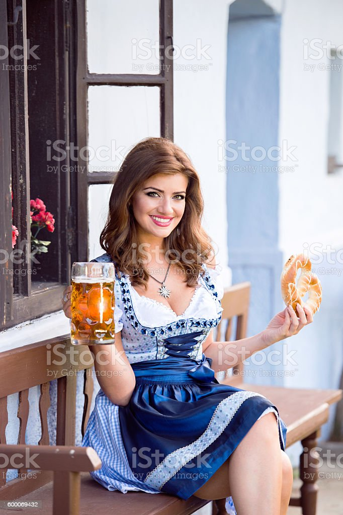 Woman in traditional bavarian dress holding beer and pretzel – Foto