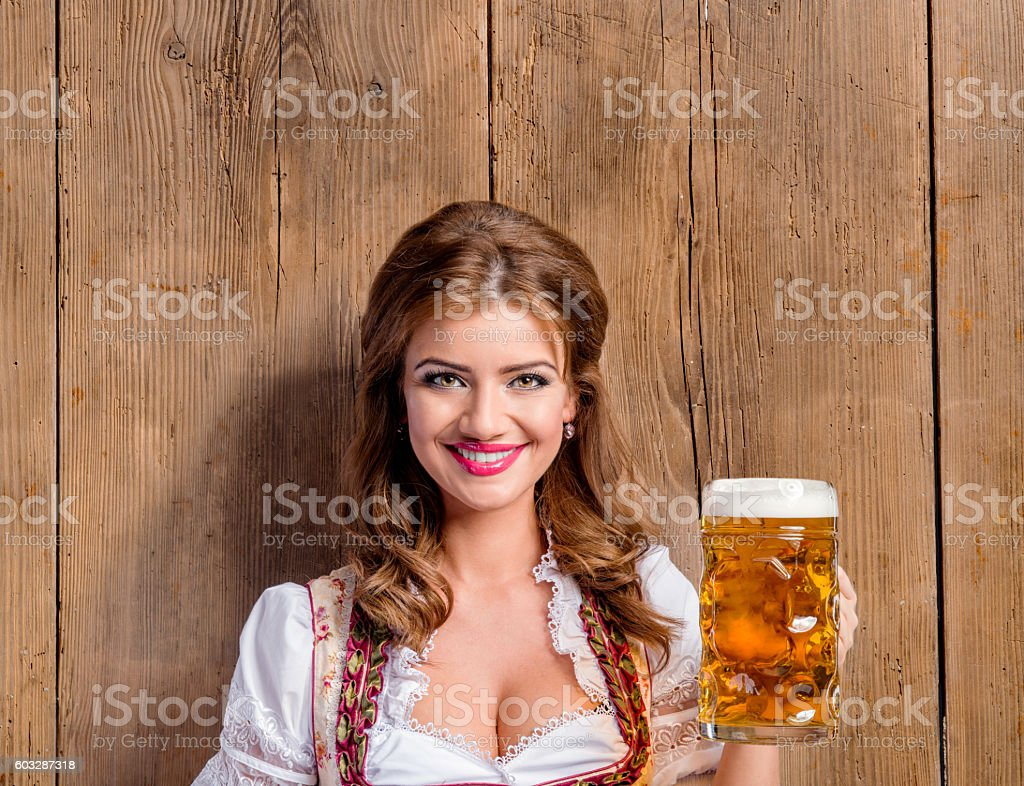 Woman in traditional bavarian dress holding beer stock photo