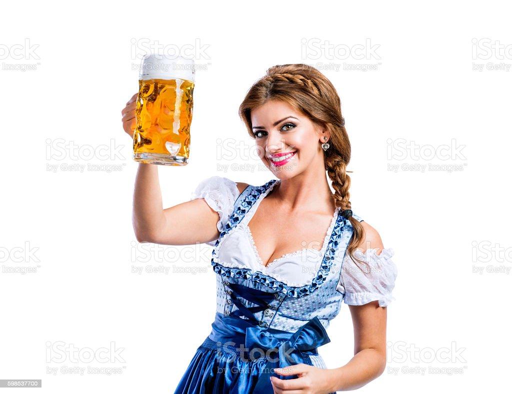 Woman in traditional bavarian dress holding mug of beer photo libre de droits