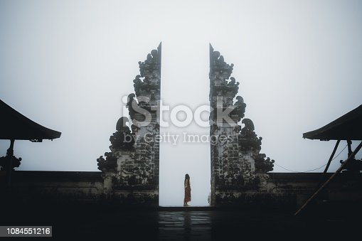 Woman in traditional Balinese clothes enjoying the foggy morning at hinduism temple on Bali island in Indonesia