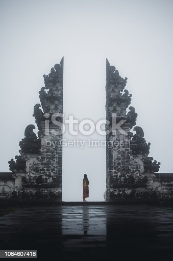 Woman in traditional Balinese clothing foes to the hinduism temple on Bali island in Indonesia
