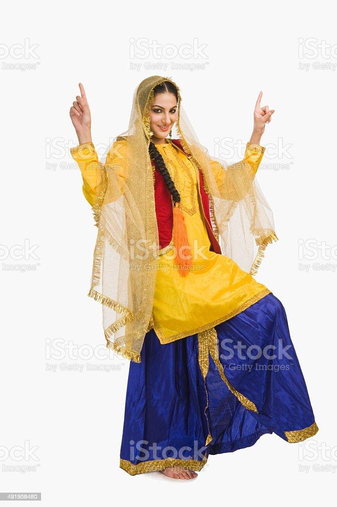 Woman in traditional yellow Punjabi dress doing bhangra stock photo