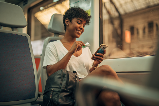 Woman sitting on a train by the window and using smart phone and credit card for shopping online