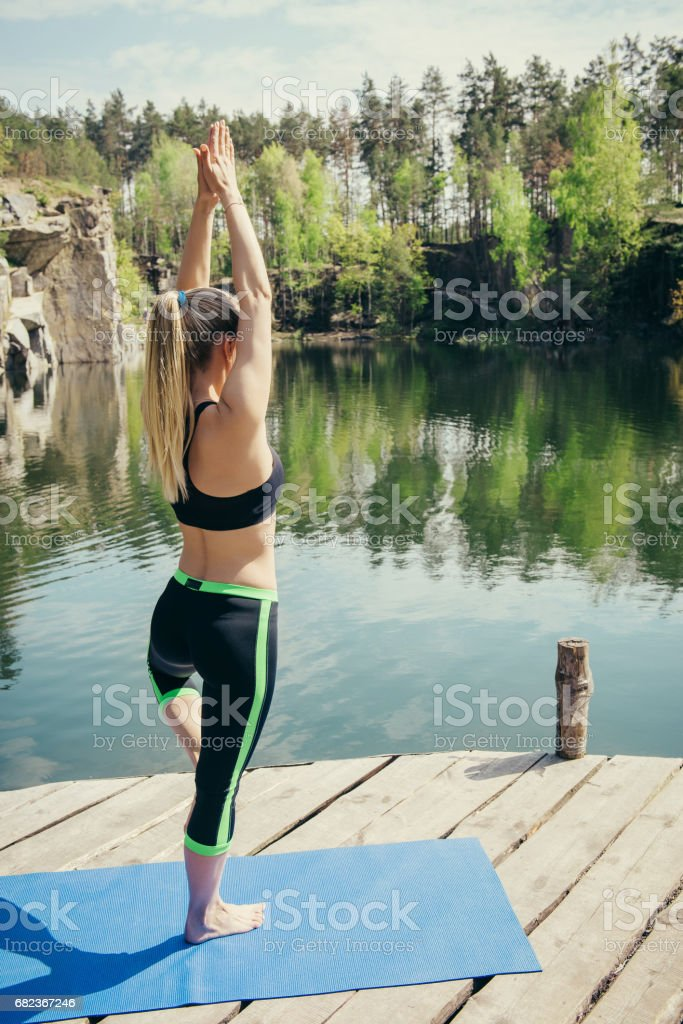 Woman in tree pose near the water during bright summer day. foto stock royalty-free