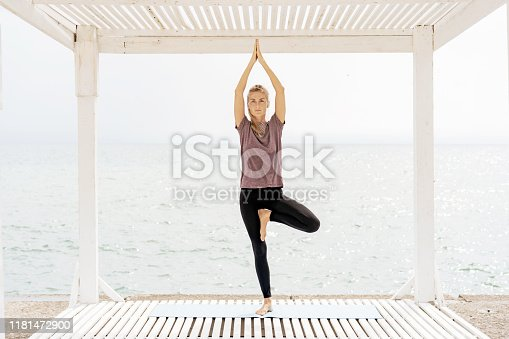 A woman in sportswear on the seashore stands in the yoga pose of a tree and holds balance on one leg.