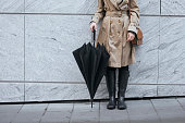 Unrecognisable woman wearing trench coat and rain boots and holding umbrella while standing outdoors.