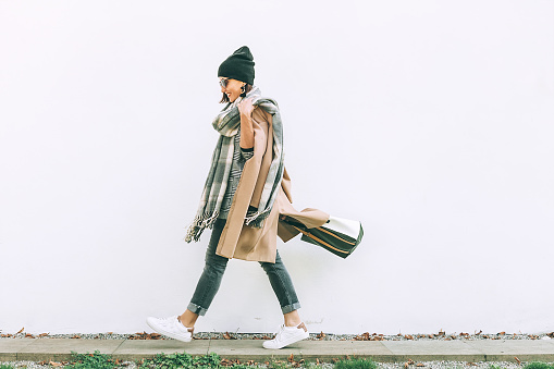 istock Woman in trend multilayered outfit walks in autumn city street. Fashion street trends 1059689010