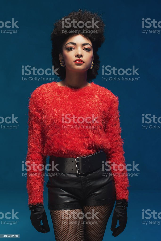Woman in trendy red and black clothes against blue stock photo