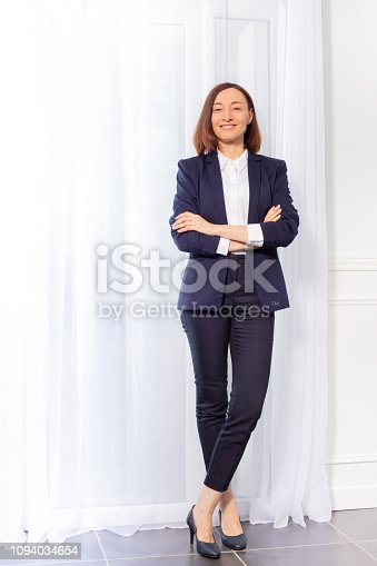 Full-length portrait of attractive woman in blue trouser suit standing with arms crossed, smiling and looking camera
