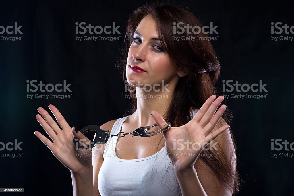 Woman in t-shirt with handcuffs looking at camera stock photo