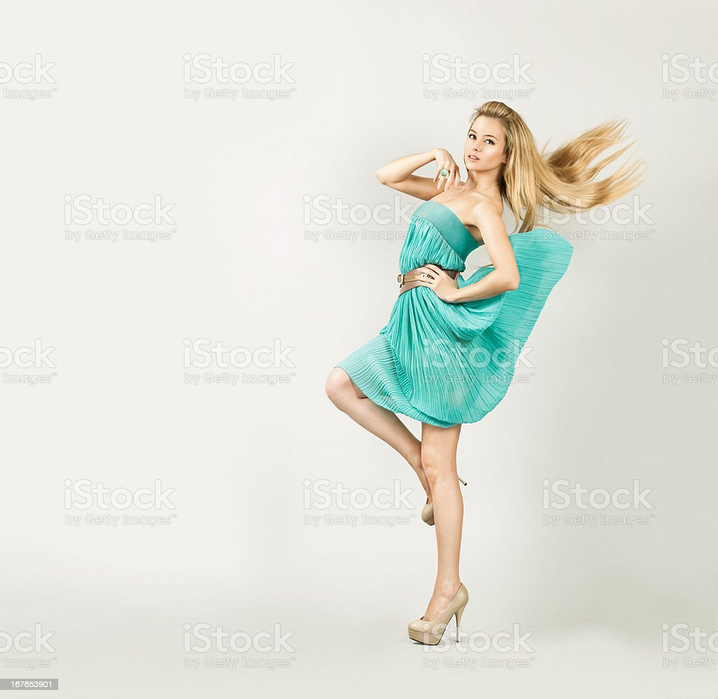 Woman in Turquoise Dress on Gray Backgound stock photo
