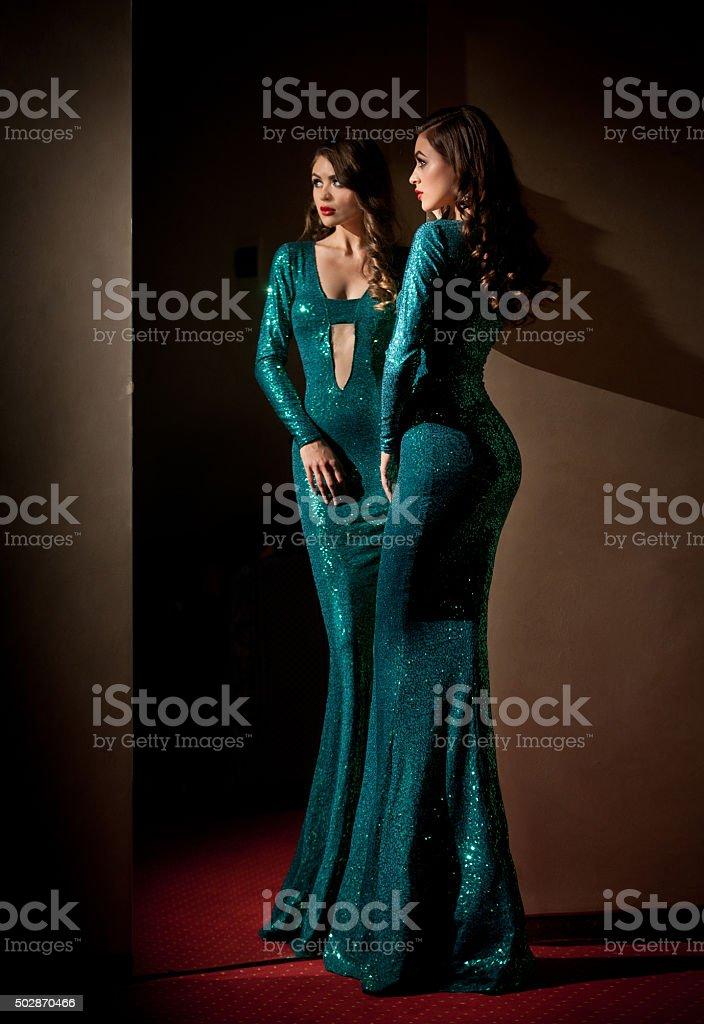 Frau in Türkis langen Kleid Blick in den Spiegel – Foto
