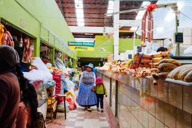 Woman in typical clothes walks with her little daughter through the Puno market in search of food stock photo