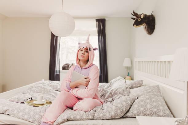 woman in unicorn costume in bedroom - unicorn bed imagens e fotografias de stock