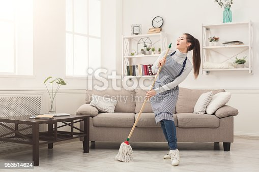 1081403344 istock photo Woman in uniform cleaning home with mop and having fun 953514624