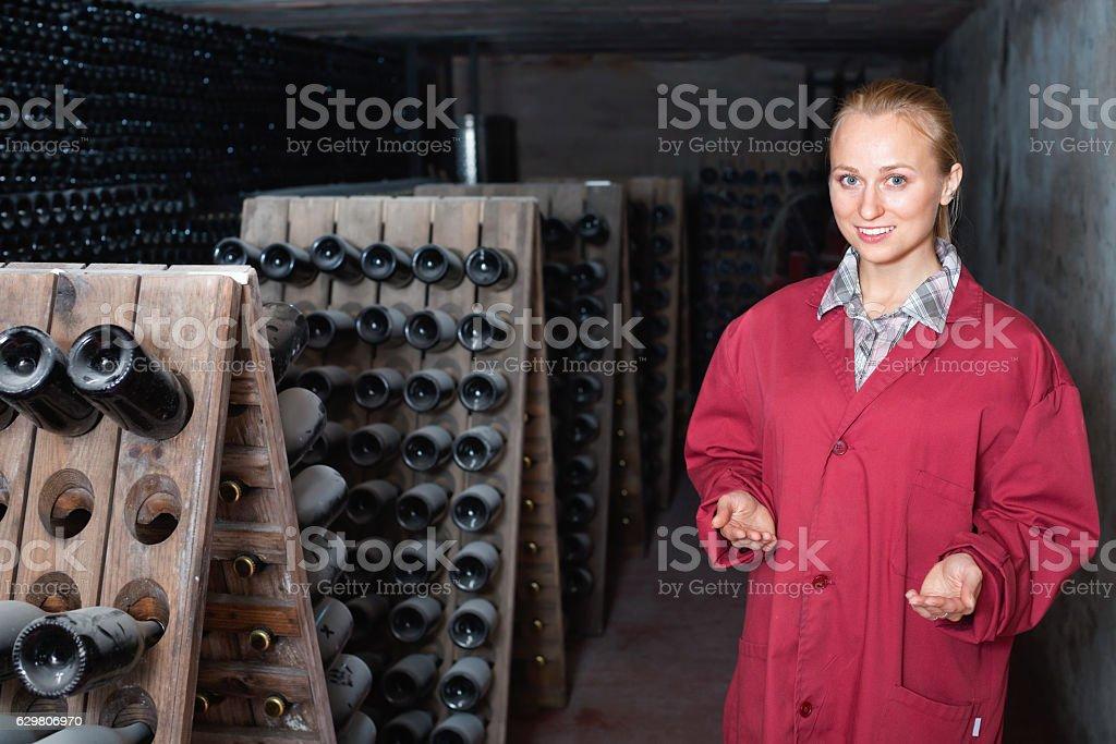 Woman in uniform working with bottle storage racks stock photo