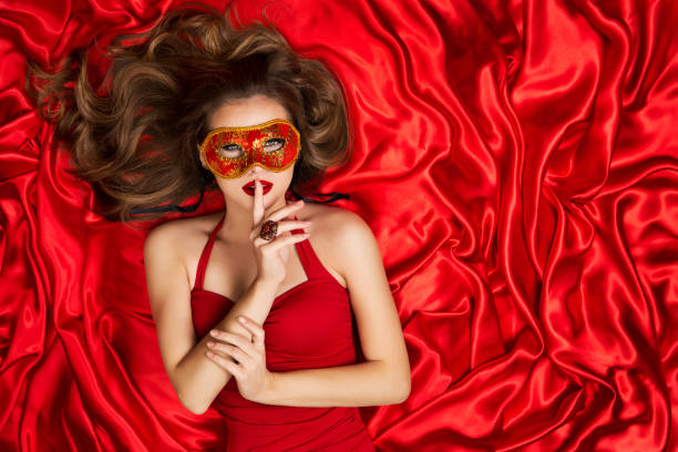 Woman in Venetian Mask Lying on Red Silk Fabric Background, Fashion Model holding Finger on Lips stock photo