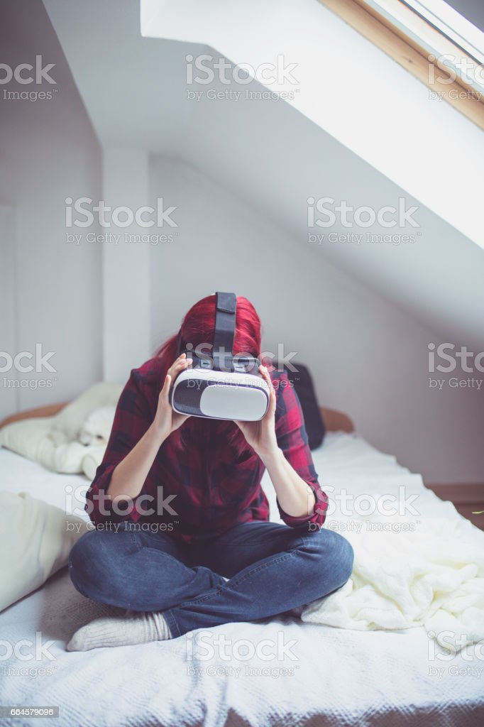 Woman in virtual reality helmet on bed. VR glasses. royalty-free stock photo