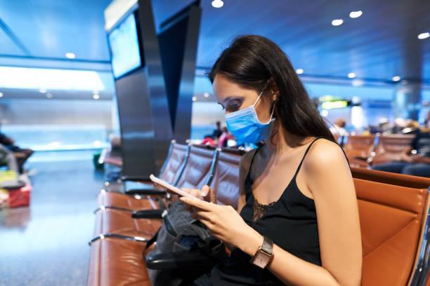 Mujer con máscara facial de protección antivirus usando un teléfono inteligente sentado en el aeropuerto vacío - foto de stock