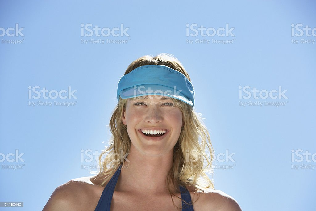 Woman in visor outdoors smiling stock photo