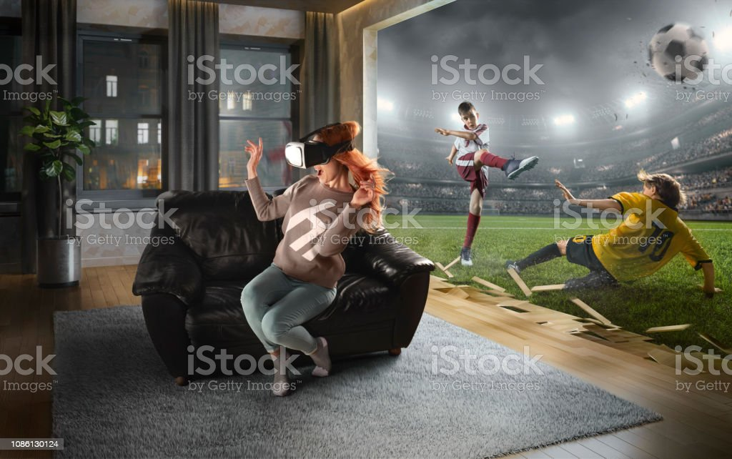 Woman in VR Glasses. Virtual Reality with children's soccer stock photo