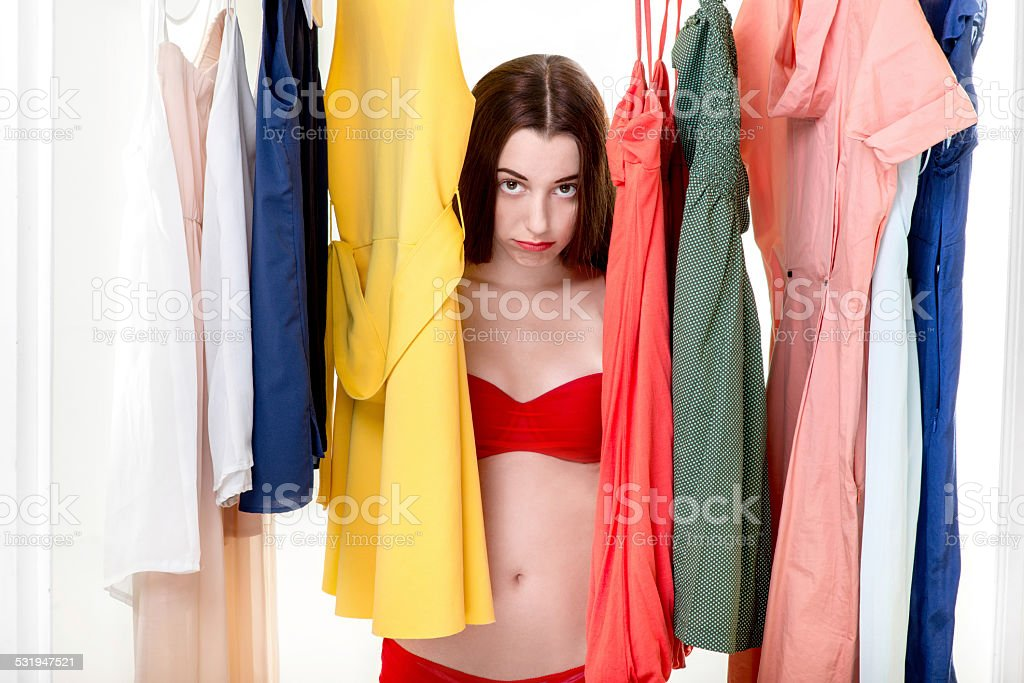 Woman in wardrobe Young sad woman in underwear thinking what dress to wear in the wardrobe. Nothing to wear concept 2015 Stock Photo