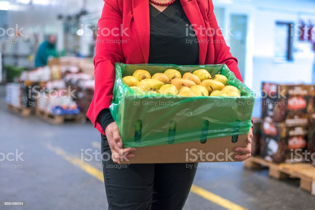 Woman in warehouse carrying a box of apples stock photo