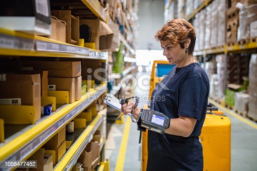 istock Woman in warehouse holding clipboard, scanning goods 1055477452