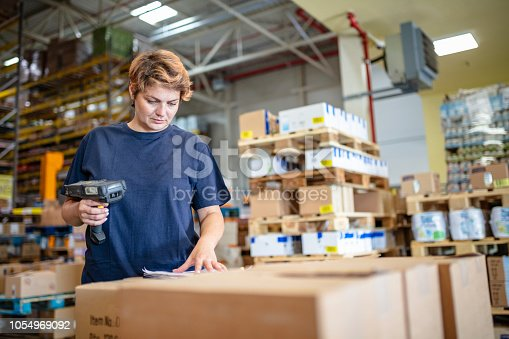 istock Woman in warehouse scanning boxes using bar code reader 1054969092