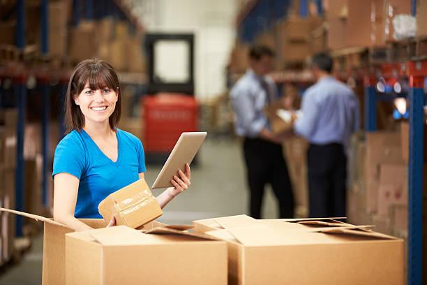 frau im warehouse kontrollkästchen mit digitalen tablet und - einzelhandelsarbeiter stock-fotos und bilder