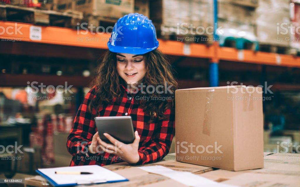 Frau im warehouse Kontrollkästchen mit digitalen tablet und – Foto