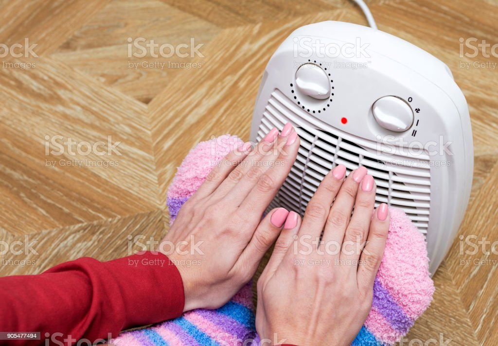 A woman in warm clothes warms her arms and legs near electric heater at home. stock photo