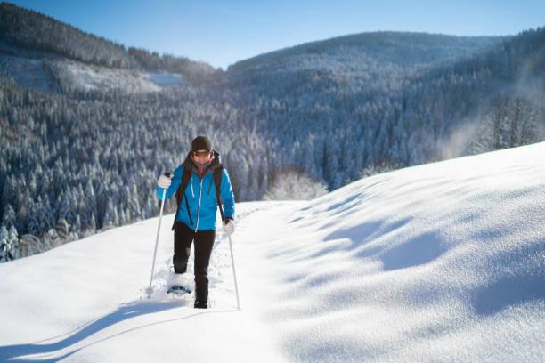 kvinna i varm vinter sportkläder njuter snöskovandring i djup snö på solig vinterdag i landsbygdens landskap - winter austria train bildbanksfoton och bilder