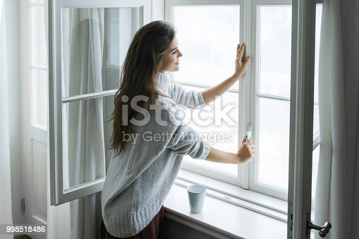 Woman is opening window to look at beautiful snowy landscape outside