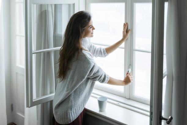 kobieta w ciepłym wełnianym swerze otwiera okno - okno zdjęcia i obrazy z banku zdjęć