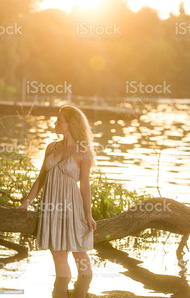 Woman in water at sunset royalty-free stock photo