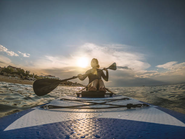 Woman in wetsuit with a paddle board stock photo