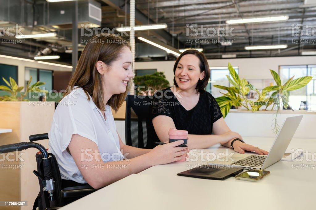 Kvinna i rullstol samarbetar i modern Office - Royaltyfri 20-29 år Bildbanksbilder