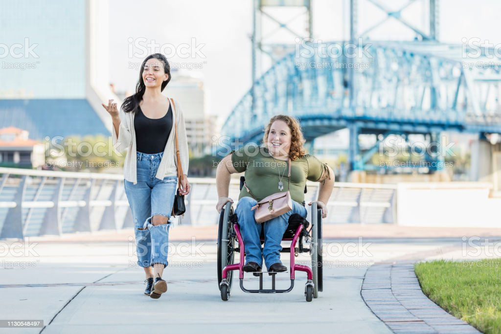 Woman in wheelchair on waterfront with Hispanic friend stock photo