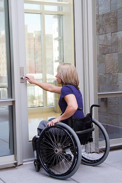 Frau im Rollstuhl öffnen Tür – Foto