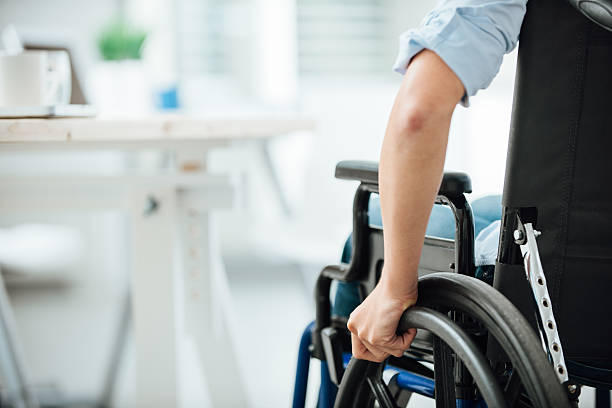 Woman in wheelchair Woman in wheelchair next to an office desk, hand close up, unrecognizable person paraplegic stock pictures, royalty-free photos & images
