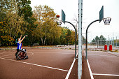 Motivated wheelchair basketball player shooting on the basketball court outdoors on bad weather day.