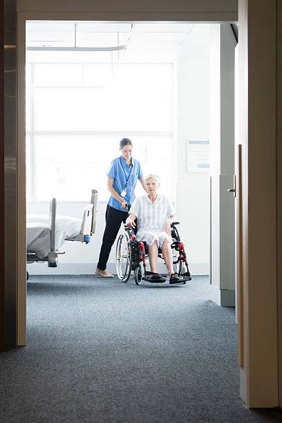 woman in wheelchair with nurse, view through open door - australian nurses stock photos and pictures